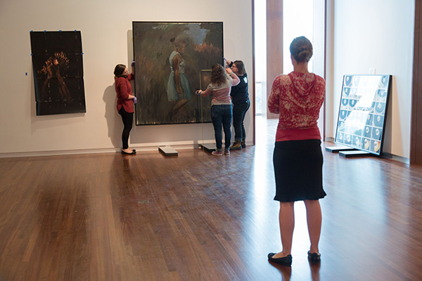 curator whitney tassie (foreground) and collections staff install british artist